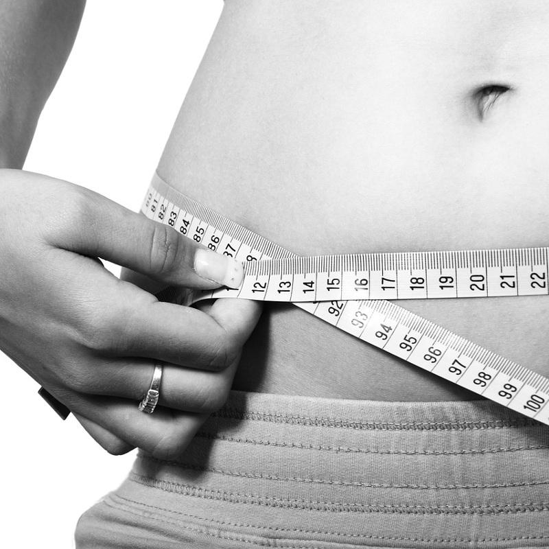 Mit Millimetermaß wird ein Bauch vermessen (schwarz/weiß)