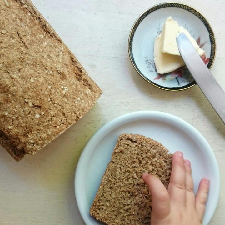 Brotleib, Brotscheibe auf Teller und Kinderhand die danach greift / Butter in einer kleinen Schale und Buttermesser