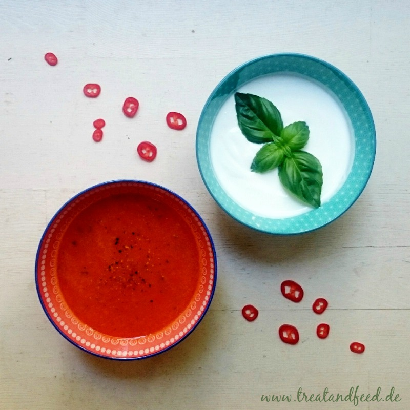 Tomatensuppe und saure Sahne mit Basilikum in kleinen Schälchen angerichtet