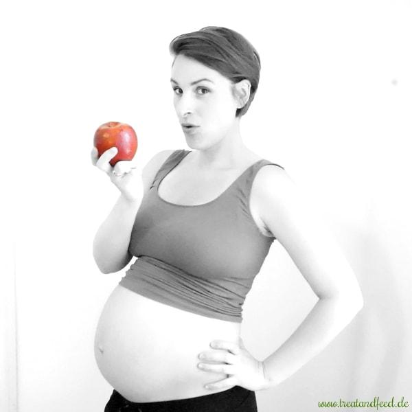 Gesunde Ernährung in der Schwangerschaft: Schwangere Frau mit einem Apfel in der Hand