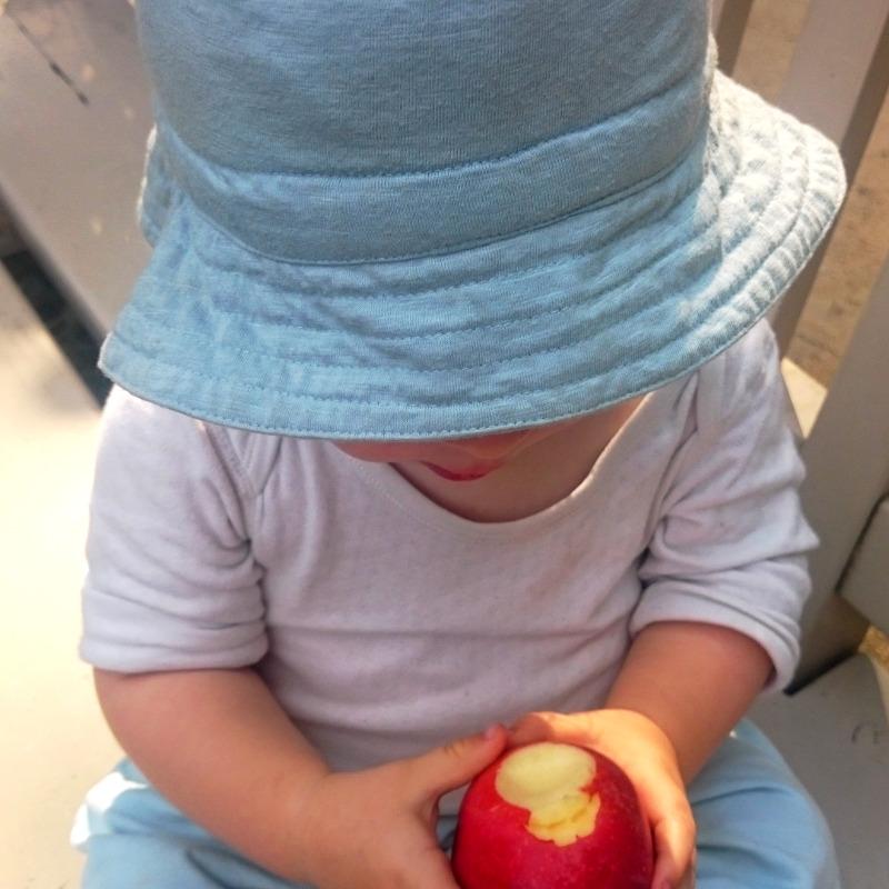 Kind mit rotem Apfel und blauem Hut