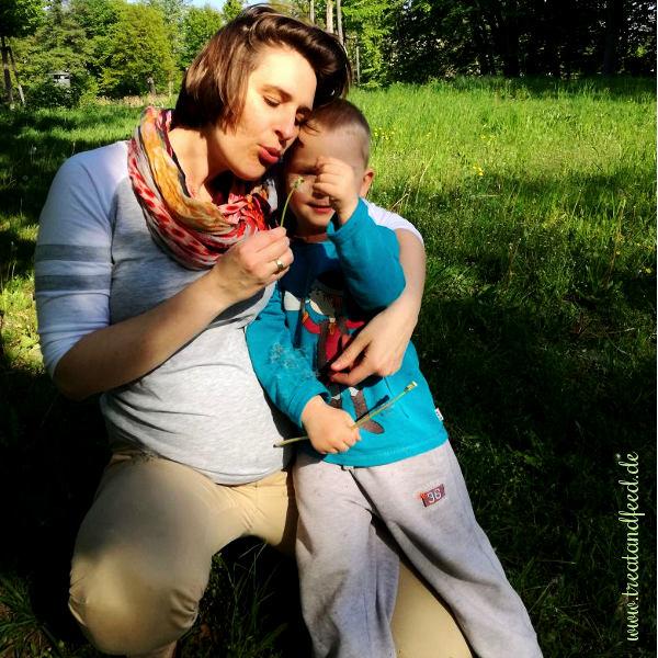 Schwangere Frau mit Kind und Pusteblume auf einer Wiese.