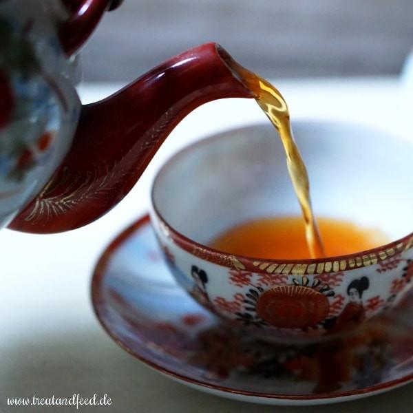 Roibuschtee wird in eine Tasse eingegossen